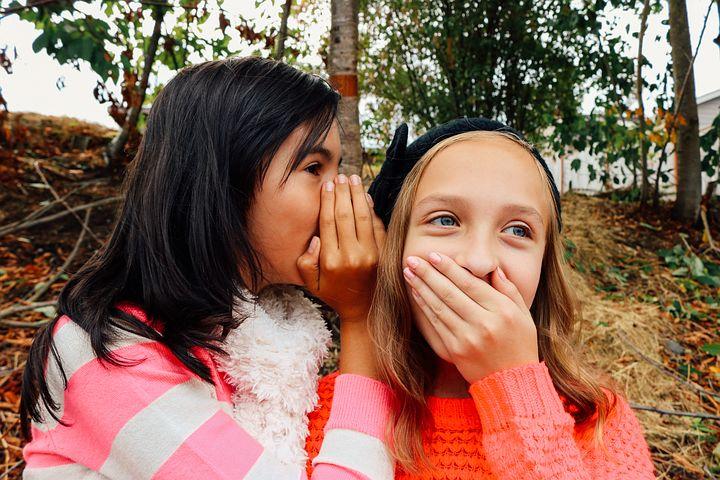 Pre-teen girls whispering